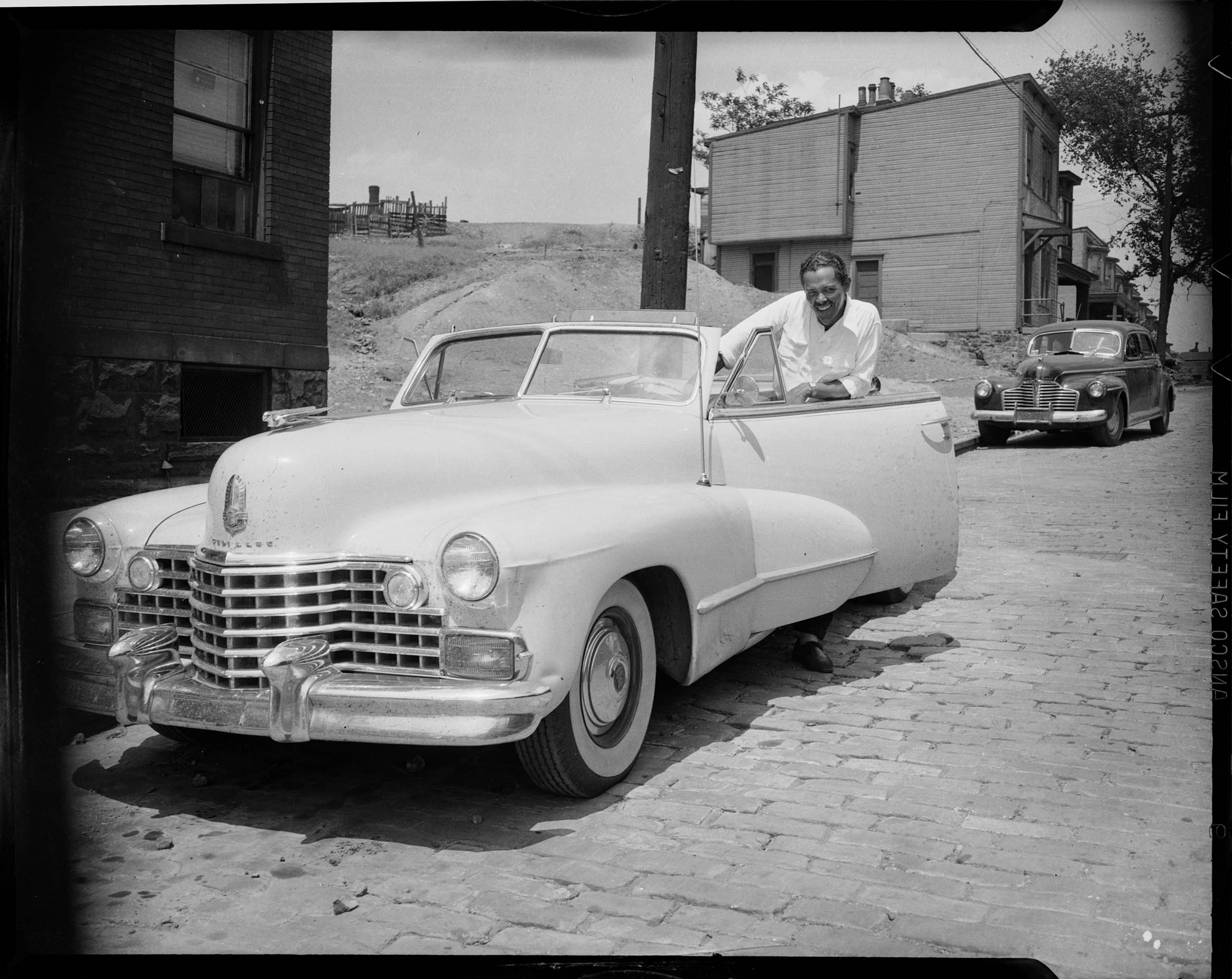 Bandleader and musician Billy Eckstine posing with Cadillac ...