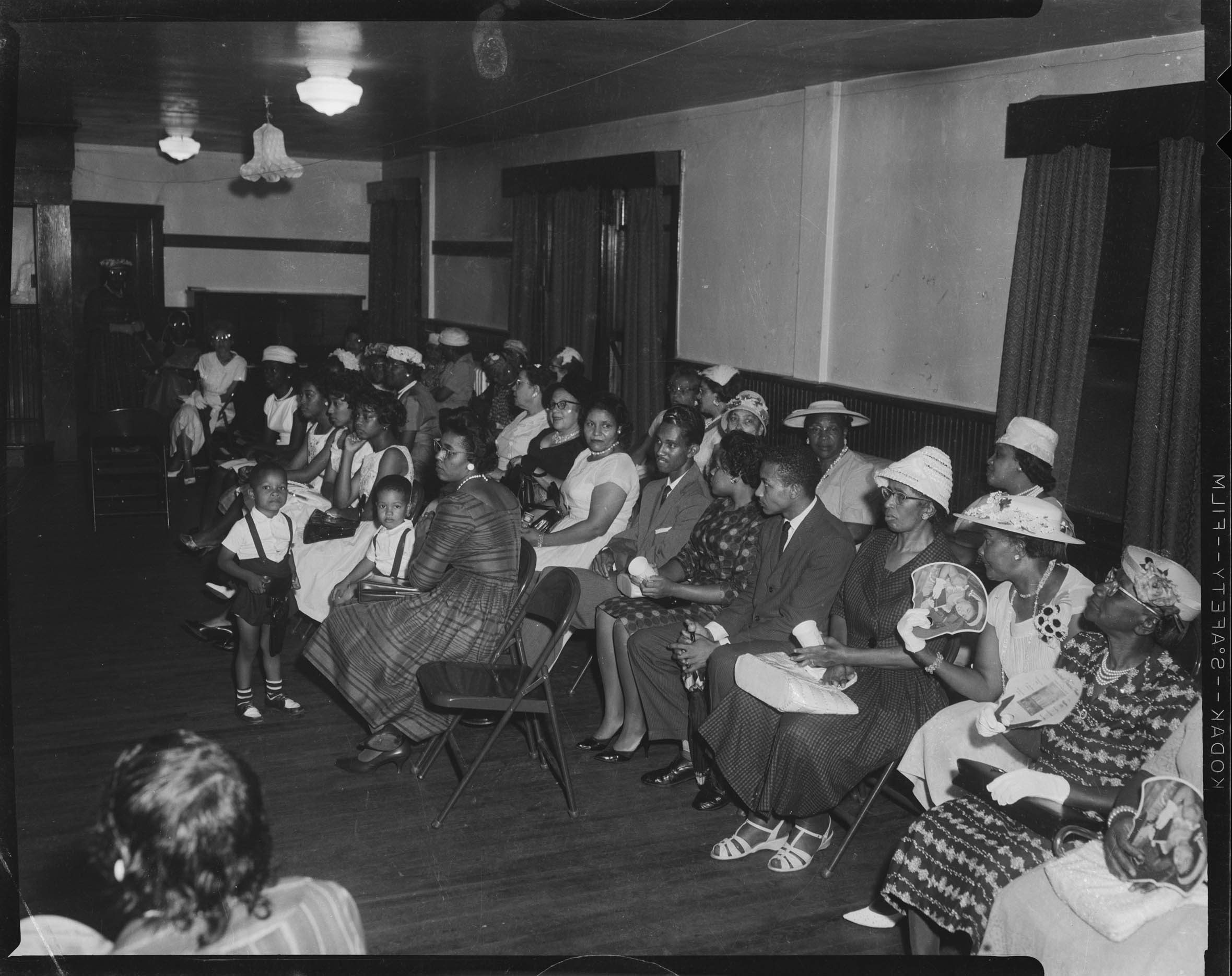 Women Men And Children Including Two Women Fanning Themselves Seated On Metal Folding Chairs Possibly For Wedding Reception In Interior With Crepe Paper Bell Decoration Cmoa Collection
