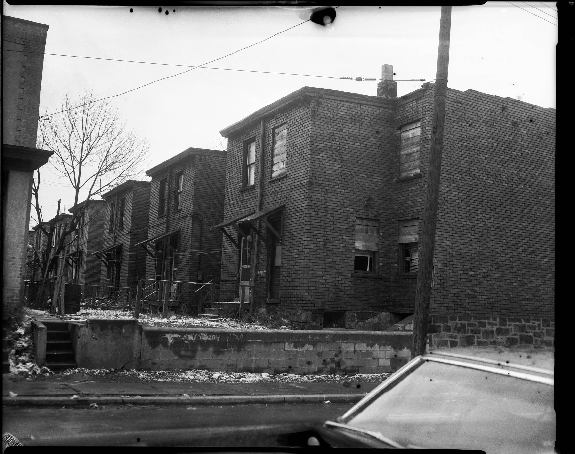 Exterior Of Rear Entrance Of Brick Row House With Awnings Over Doors And Cinder Block Wall In Back Yard Of End Unit Possibly Susquehanna Street Cmoa Collection