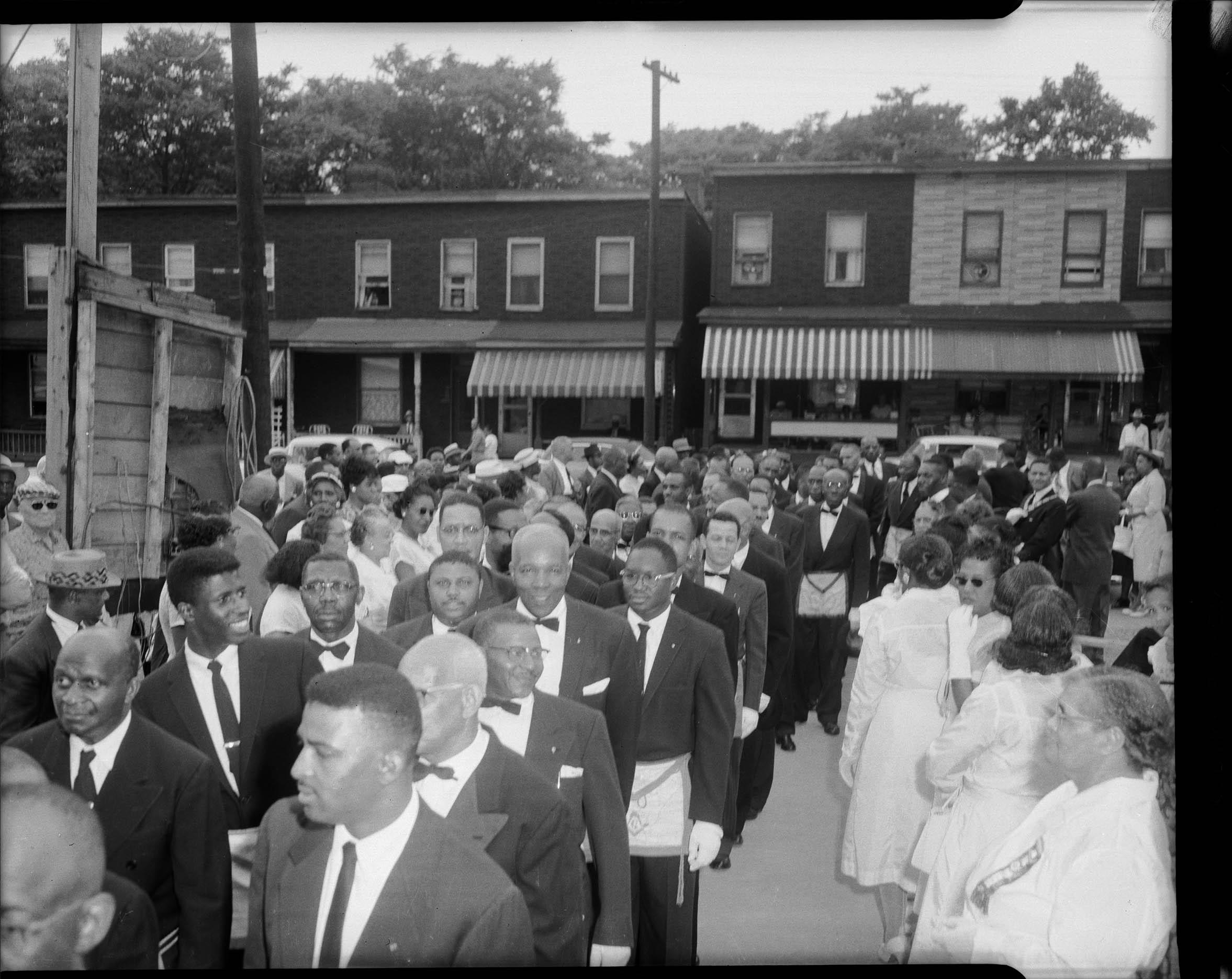 Men wearing Masonic aprons, walking in group, with men and women
