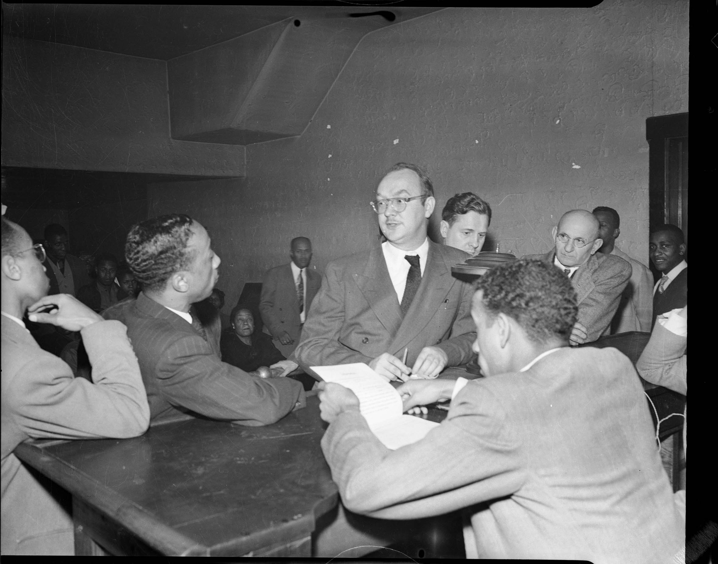 f0dcf35c Men, including one wearing eyeglasses, pinstriped suit, and patterned  necktie, standing at desk with round lamp, in Alderman Harry B.  Fitzgerald's office