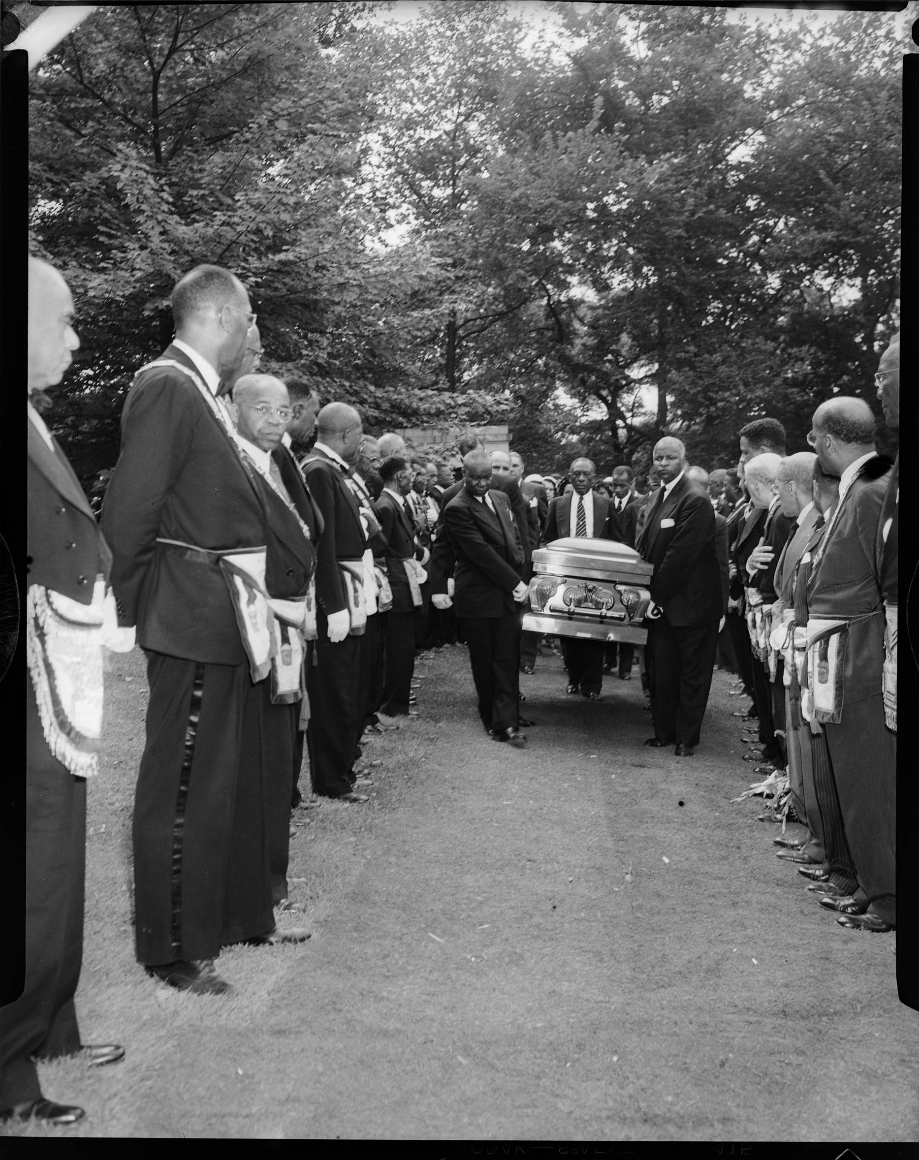 Pallbearers carrying casket through row of men wearing Masonic